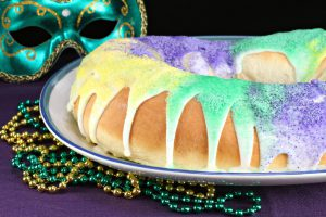Close up of a festive King's Cake to celebrate Mardi Gras.  Fat Tuesday beads and a mask around the cake.
